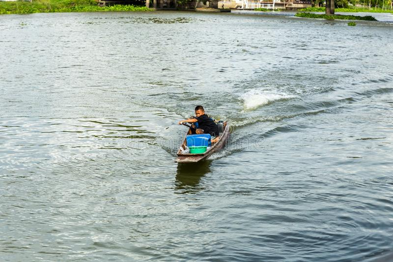 Nakhon Pathom/Thailand - Mei 26 2018: De jongensaandrijving een motorboot, kind controleert skillfully een motorboot in de rivier stock afbeeldingen