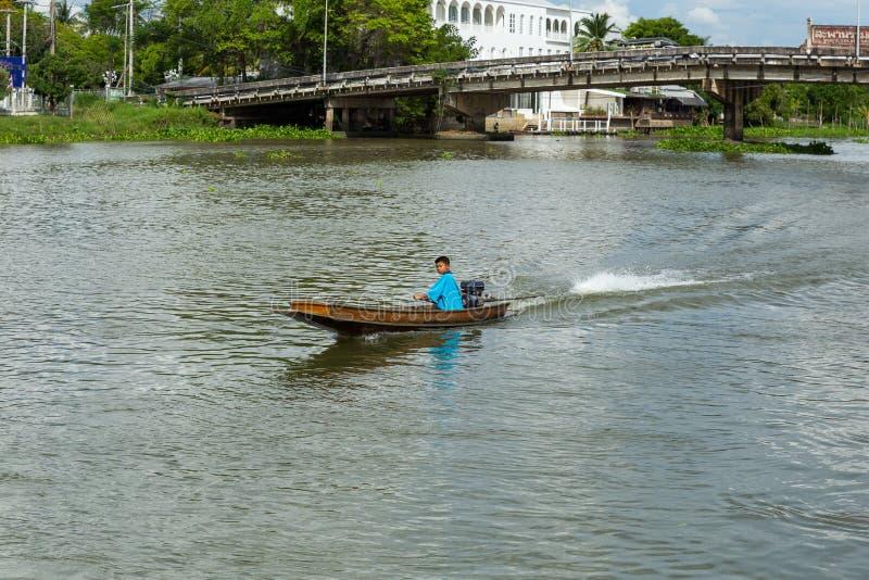 Nakhon Pathom/Thailand - Mei 26 2018: De jongensaandrijving een motorboot, kind controleert skillfully een motorboot in de rivier royalty-vrije stock foto