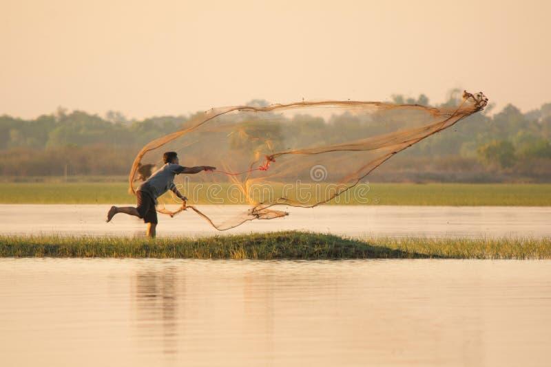 NAKHON PHANOM, TAILÂNDIA - 4 de novembro de 2018: Pescador que molda uma rede no lago fotografia de stock royalty free