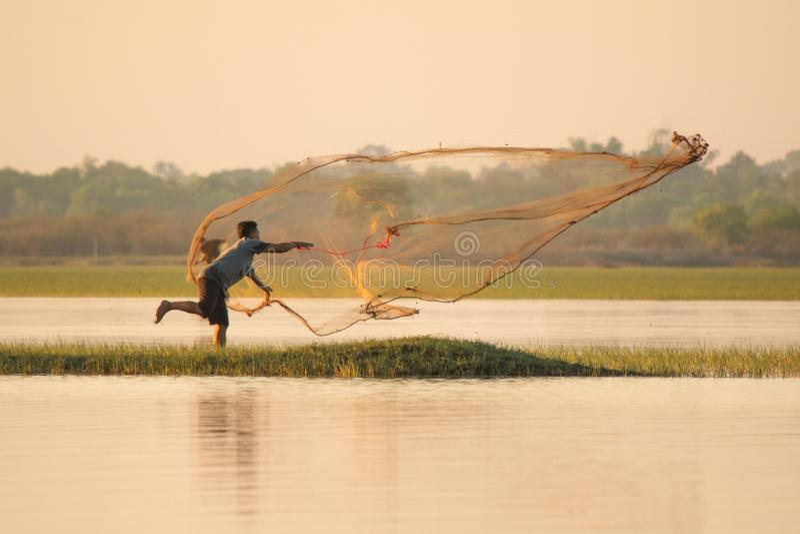 NAKHON PHANOM, THAÏLANDE - 4 novembre 2018 : Pêcheur moulant un filet dans le lac photographie stock libre de droits