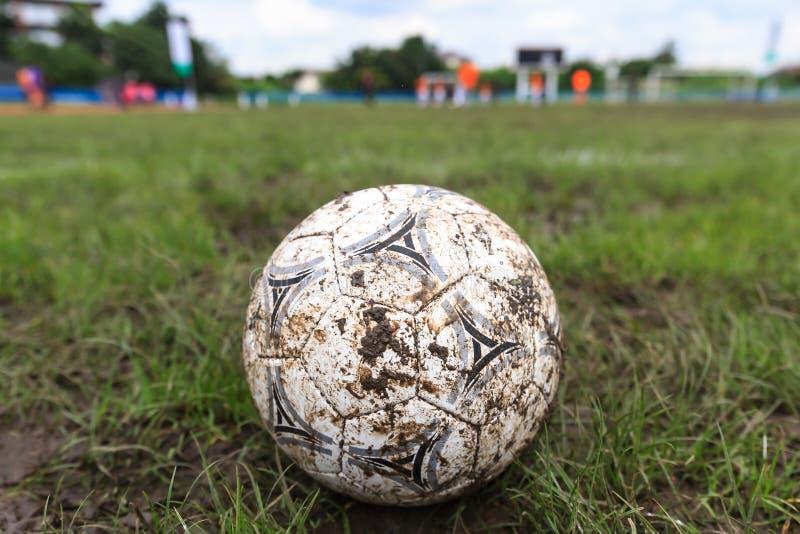 Nakhon Ratchasima, Tailândia - 1º de outubro: Bola de futebol enlameada em um campo de futebol no estádio municipal Nakhon Ratcha imagem de stock royalty free