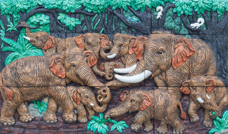 Nakhonnayok, THAILAND - May 3, 2015 : Antique decorate wall : Elephants playing in the forest. Nakhonnayok, THAILAND - May 3, 2015 : Antique decorate wall stock images