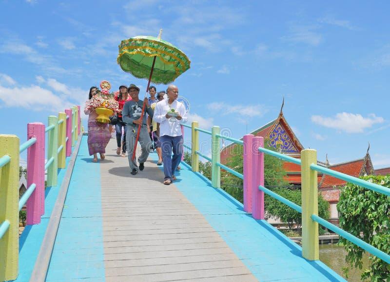 NAKHONPATOM, THAILAND - JUNI 24, 2017: De plaatselijke bewoners paraderen op een regenboog-gekleurde brug met monnik-aan-leiden v royalty-vrije stock afbeelding