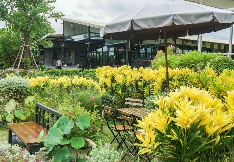 Nakornpathom/Thailand - Juni 26 2019: openluchtstoel en lijst in koffiewinkel in tropische tuin royalty-vrije stock foto's