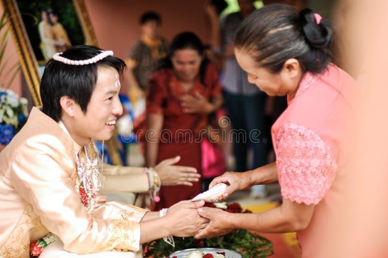 NAKORNRACHASIMA,泰国- 7月:在婚礼的未认出的夫妇7月21,2013在Nakornrachasima,泰国。保佑的wate 免版税库存图片