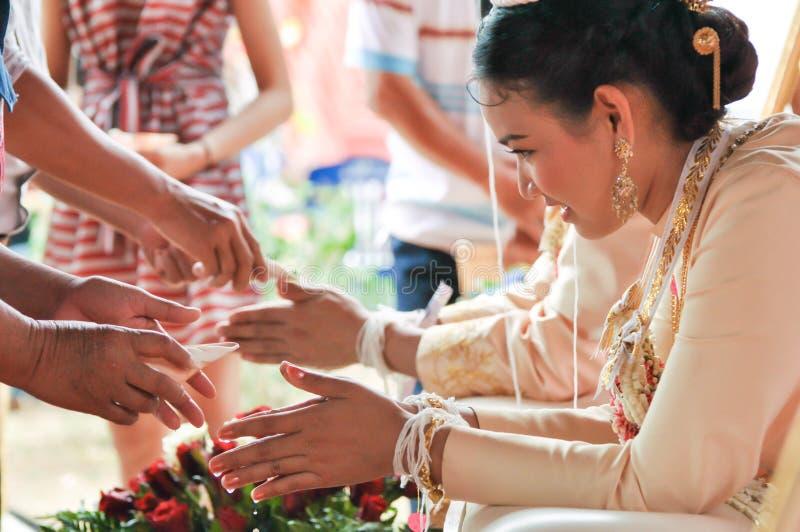 NAKORNRACHASIMA,泰国- 7月:在婚礼的未认出的夫妇7月21,2013在Nakornrachasima,泰国。保佑的wate 免版税库存照片
