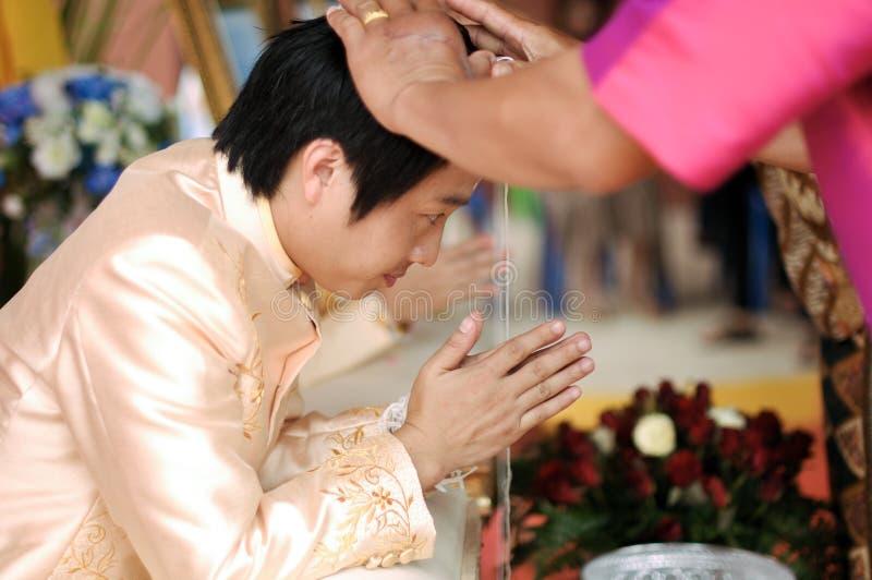 NAKORNRACHASIMA,泰国- 7月:在婚礼的未认出的夫妇7月21,2013在Nakornrachasima,泰国。新郎h 库存照片
