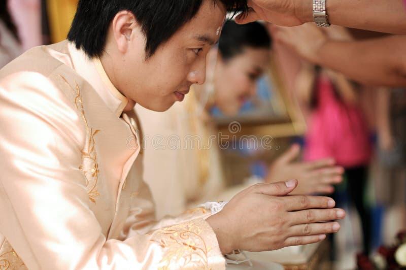 NAKORNRACHASIMA,泰国- 7月:在婚礼的未认出的夫妇7月21,2013在Nakornrachasima,泰国。新郎h 免版税库存照片