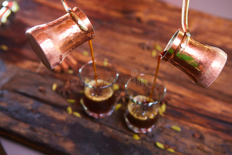Nalewać arabską kawę w filiżankach na drewnianym tle fotografia royalty free