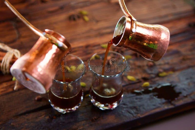 Nalewać arabską kawę w filiżankach na drewnianym tle zdjęcia stock