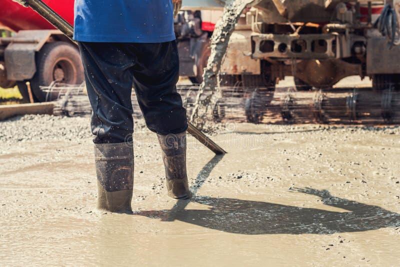 nalewać beton z pracownik mieszanki cementem przy budową obraz stock