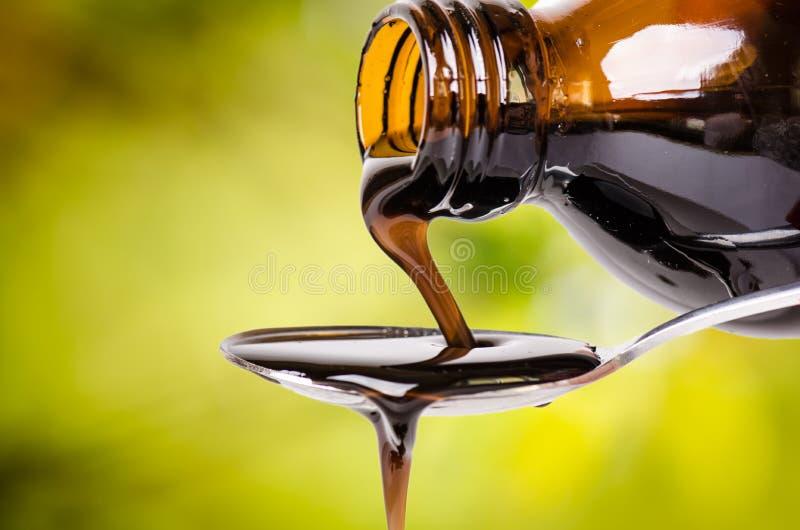 Nalewać ciecz na łyżce zielony środowisk naturalnych Apteka i zdrowy tło Medycyna Kasłanie i zimny lek obrazy stock