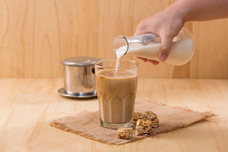Nalewać dojny szkło kawa na drewnianym stole wewnątrz obraz stock