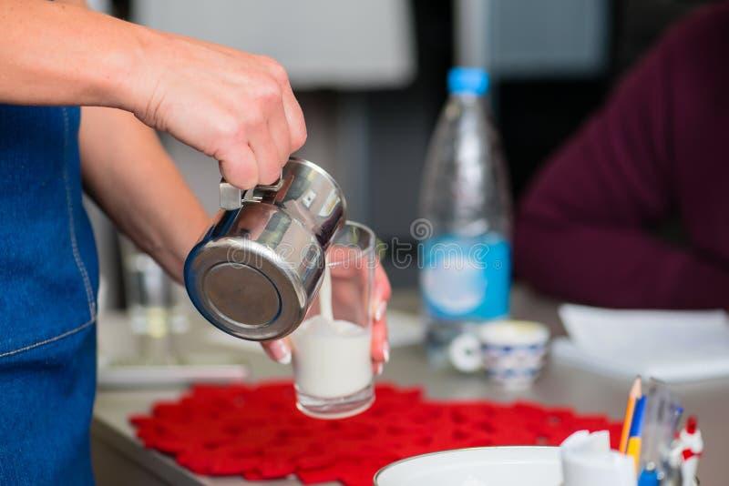Nalewać mleko w filiżance fotografia stock