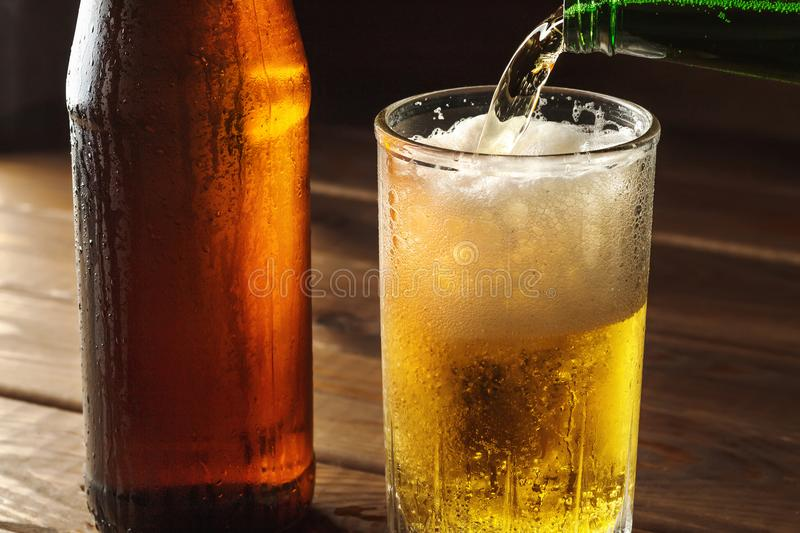 Nalewać pieniącego piwo w szklanego kubek z kroplami blisko zimnego piwa bootle na drewnianym stole, rzemiosła piwowarstwo obrazy stock