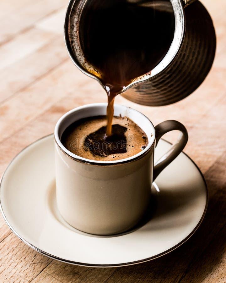 Nalewać Turecką kawę w filiżankę zdjęcie royalty free