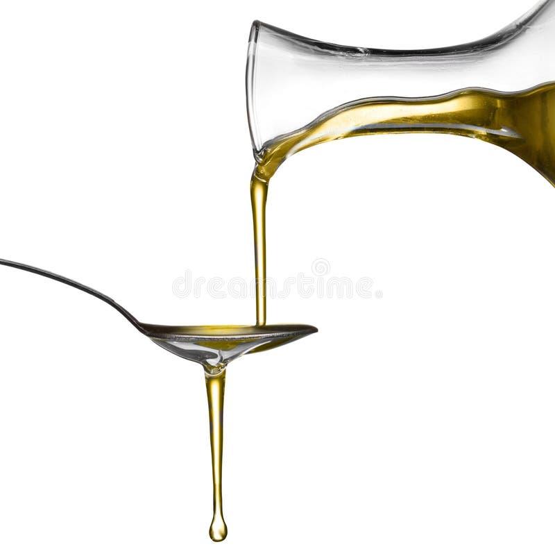 Nalewa olej na łyżce odizolowywającej zdjęcie stock