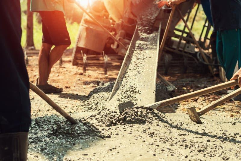 nalewający beton z pracownik mieszanki cementem dla budować drogę przy przeciwem zdjęcia royalty free