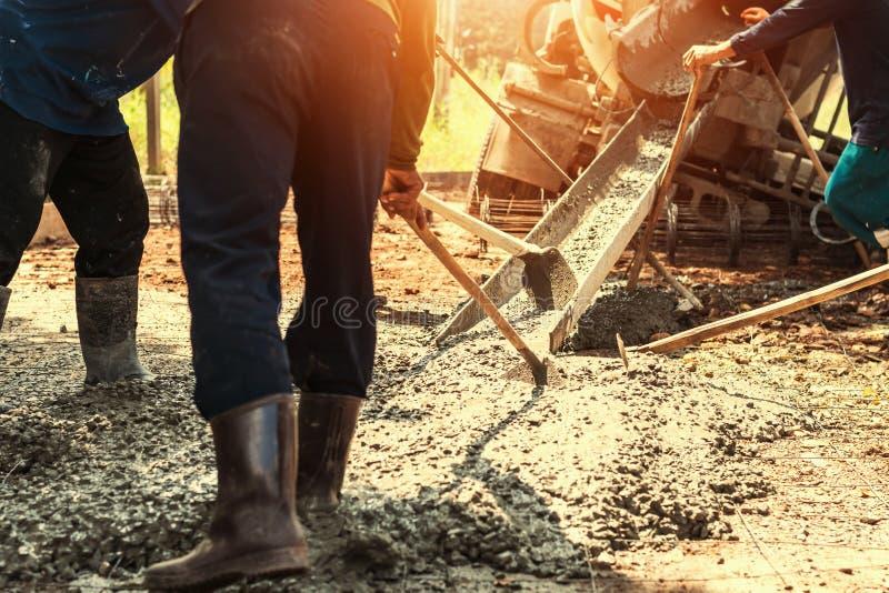 nalewający beton z pracownik mieszanki cementem dla budować drogę przy przeciwem zdjęcie stock
