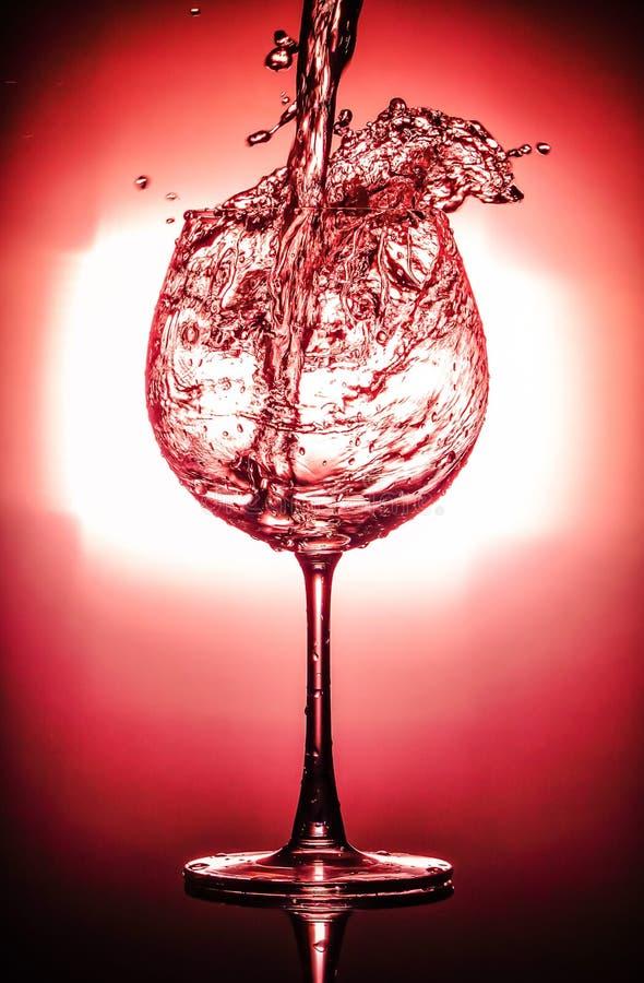 Nalewający wodę, pluśnięcie w szkło z szkła odizolowywającego na jaskrawym tle i obraz stock