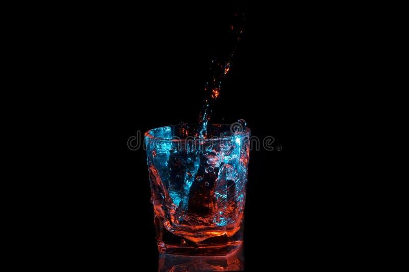Nalewający wodzie w skał szklany poniższy błękitne i pomarańczowy światła odizolowywających na czarnym tle obrazy royalty free