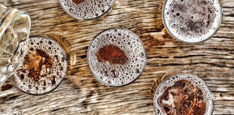 nalewanie piwa szkła z piwo stojakiem na drewnianym stole na widok zbliżenie zdjęcia royalty free