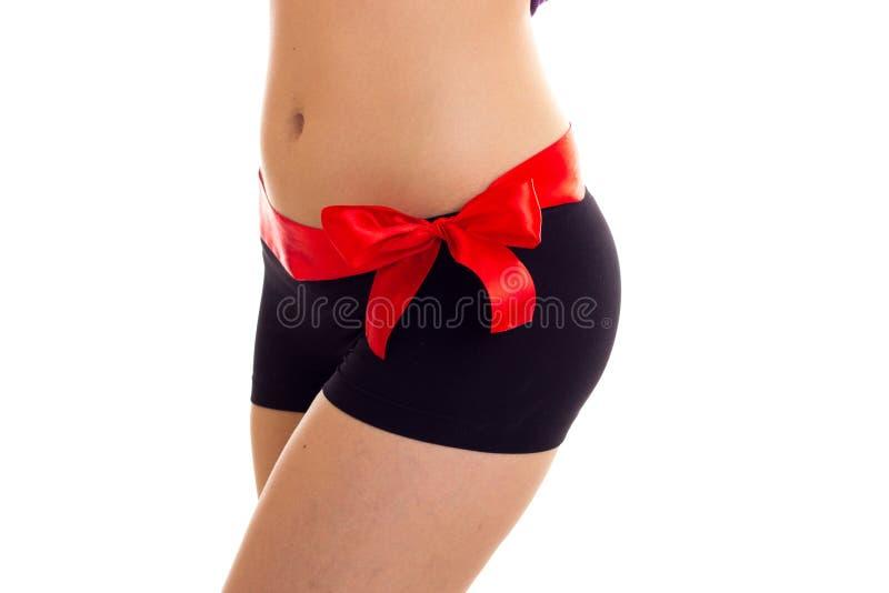 Nalgas del ` s de la mujer con el bowtie rojo foto de archivo libre de regalías