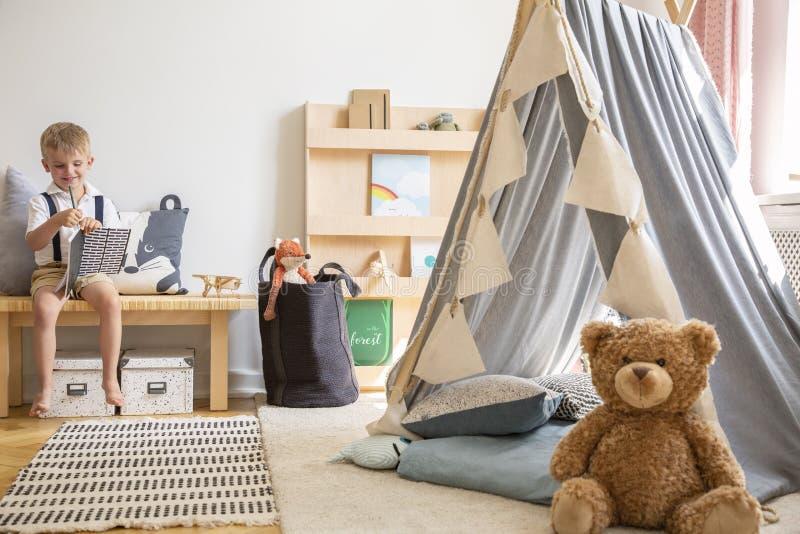 Nallebjörn bredvid det gråa scandinavian tältet i stilfulla pojkes sovrum med möblemang som göras från naturliga material, verkli royaltyfri bild