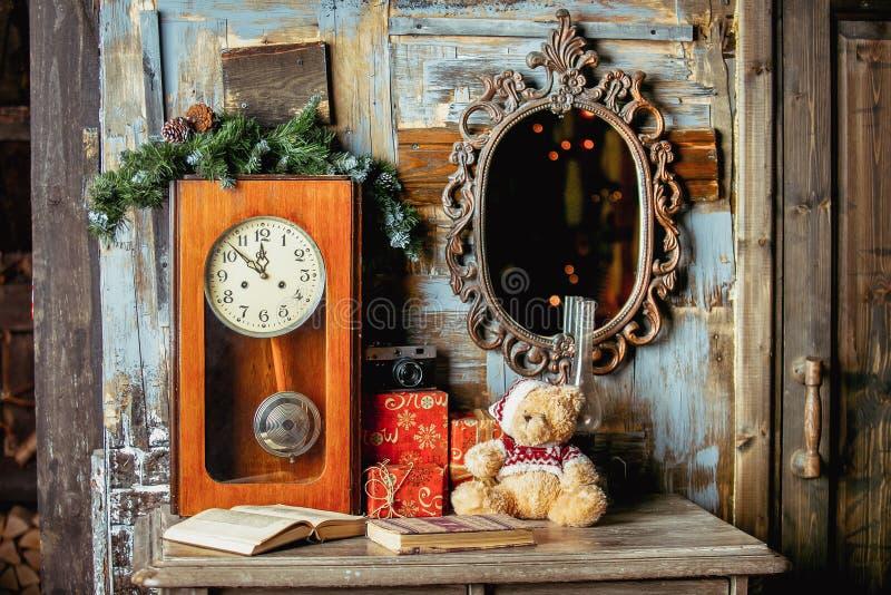 Nallebjörn, gåvor, böcker, tappningklocka och spegel på en träbakgrund i rummet som dekoreras för jul Ferielynne Lyckligt fotografering för bildbyråer
