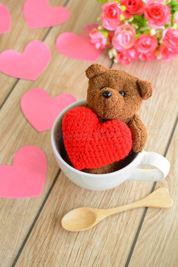 Nallebjörn i kopp kaffe med röd hjärtaform på trätabellen royaltyfri fotografi