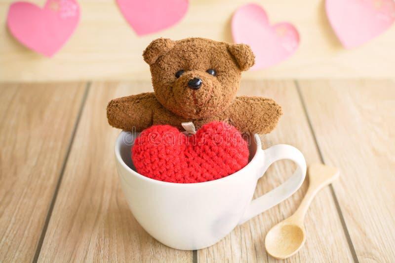 Nallebjörn i kopp kaffe med röd hjärtaform på trätabellen arkivfoton