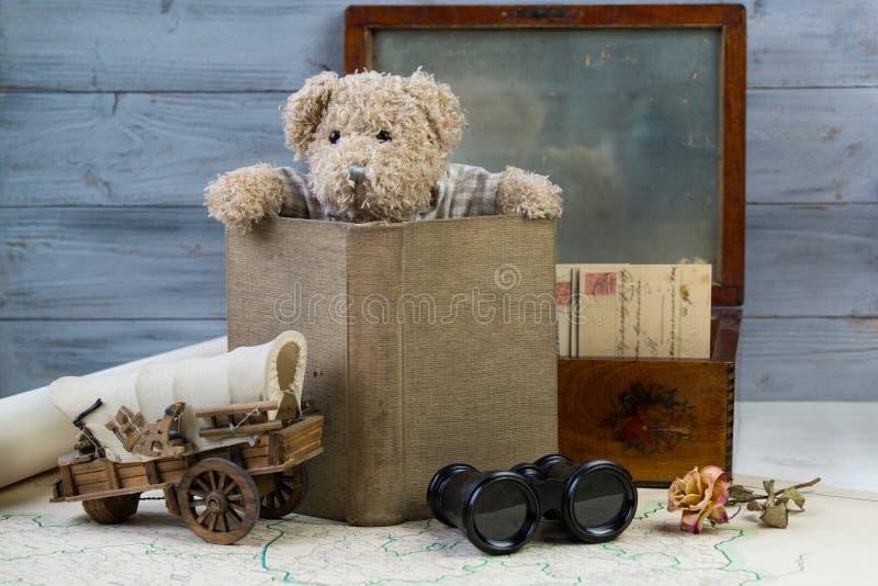 Nallebjörn med den gamla boken, stolpeasken med antikvitetbokstäver och den gamla översikten med kikare arkivfoto