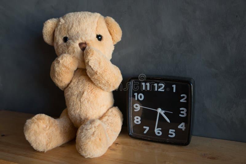 Nallebjörn med klockan, nallebjörn som sitter på trägolv mot arkivfoton