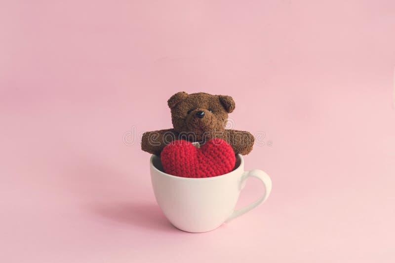 Nallebjörn med röd hjärtaform i kopp kaffe arkivbild