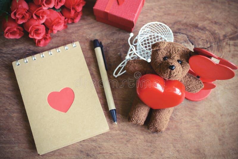 Nallebjörn med röd hjärtaform och anteckningsbok på gammal träbackg arkivbild