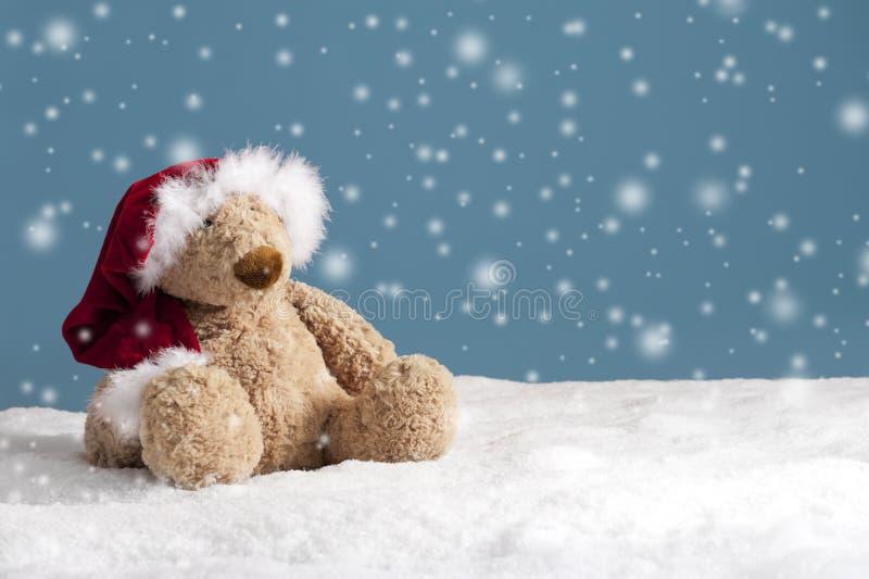Nallebjörn med xmas-hatten i korrekt läge i snowen royaltyfri fotografi
