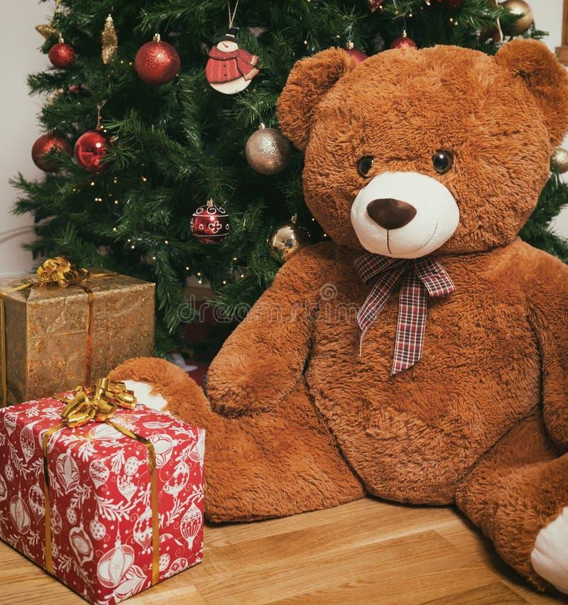 Nallebjörn nära julträd med gåvor arkivbild