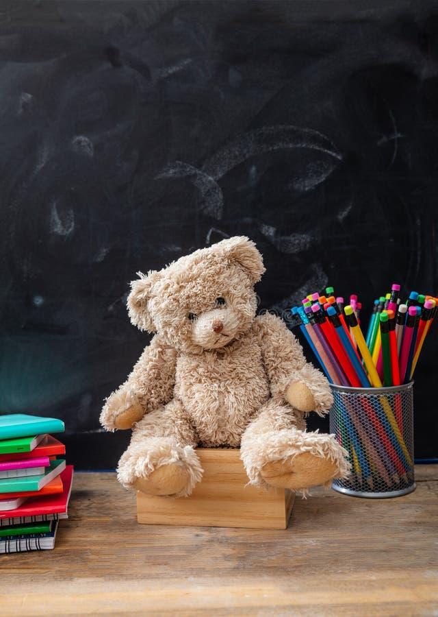 Nallebjörn och färgrika blyertspennor och anteckningsböcker på svart tavlabakgrund, kopieringsutrymme arkivfoto