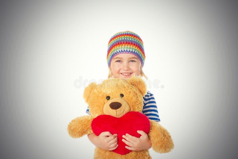 Nallebjörn och hjärta för liten flicka hållande royaltyfri bild