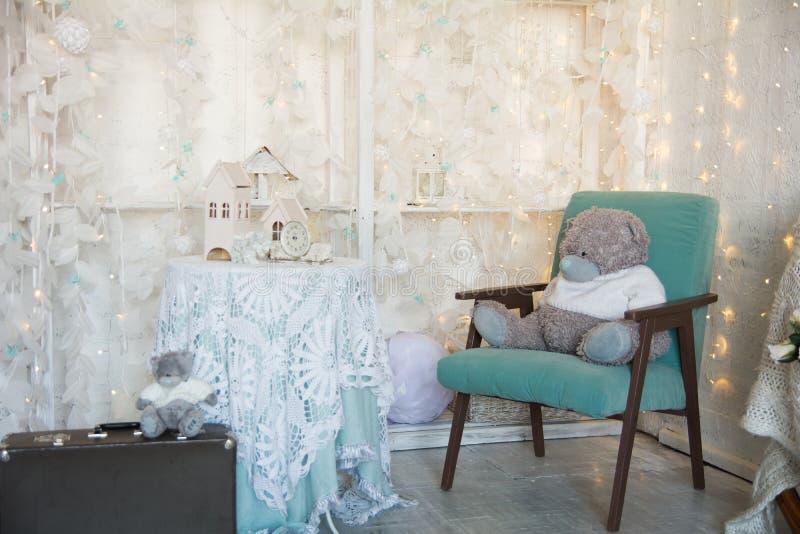 Nallebjörn på en gammal stol och ett leksakhus med klockan på tabellen Resväska med en björn på en ljus feriebakgrund royaltyfria bilder