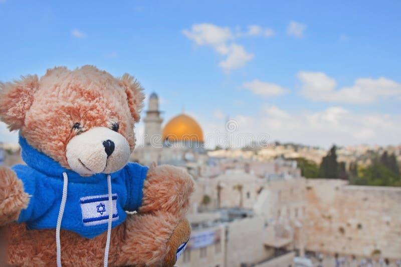 Nallebjörn på en solig dag på bakgrunden av Goldenet Dome och den att jämra sig väggen i Jerusalem Leka med flaggan av Israel royaltyfria foton