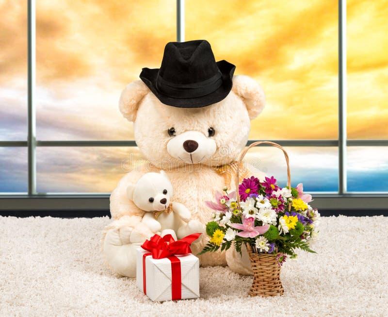 Nallebjörn som är iklädd en hatt, en överraskninggåva och korg av blommor på solnedgången Den panorama- Windows arkivbilder