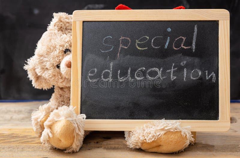 Nallebjörn som döljer bak en svart tavla Specialundervisningtextteckning på svart tavla arkivbilder