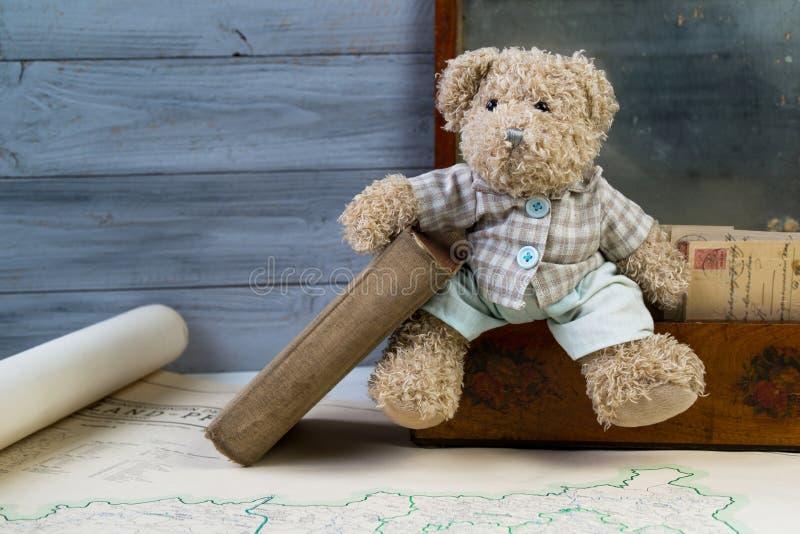 Nallebjörn som rymmer den gamla boken på tappningasken med gamla vykort royaltyfri fotografi