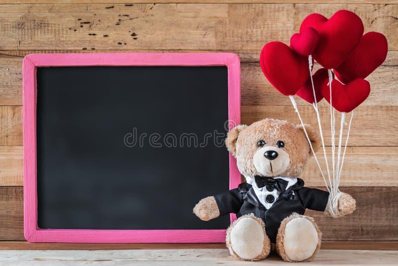Nallebjörn som rymmer denformade ballongen royaltyfria bilder