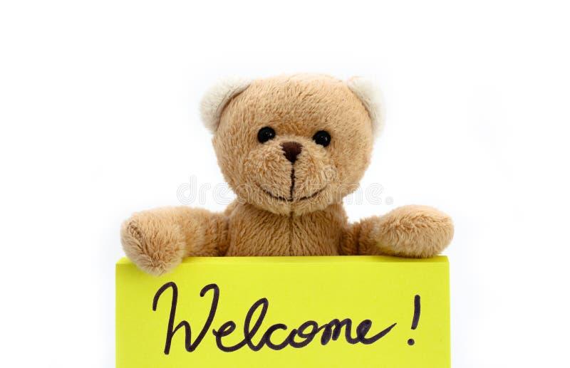 """Nallebjörn som rymmer med de två händerna en anmärkning i ljus gul färg med den handskrivna meddelande""""Welcomen! """" som välkom royaltyfria bilder"""