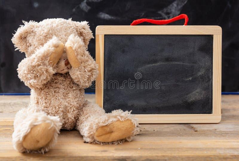 Nallebjörn som täcker ögon och en tom svart tavla, utrymme för text royaltyfri foto
