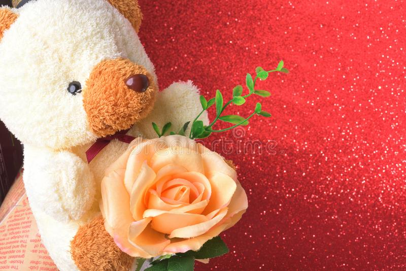 Nallebjörnen med blommor i valentindag på rött blänker suddig abstrakt bakgrund för bokehljus arkivfoton