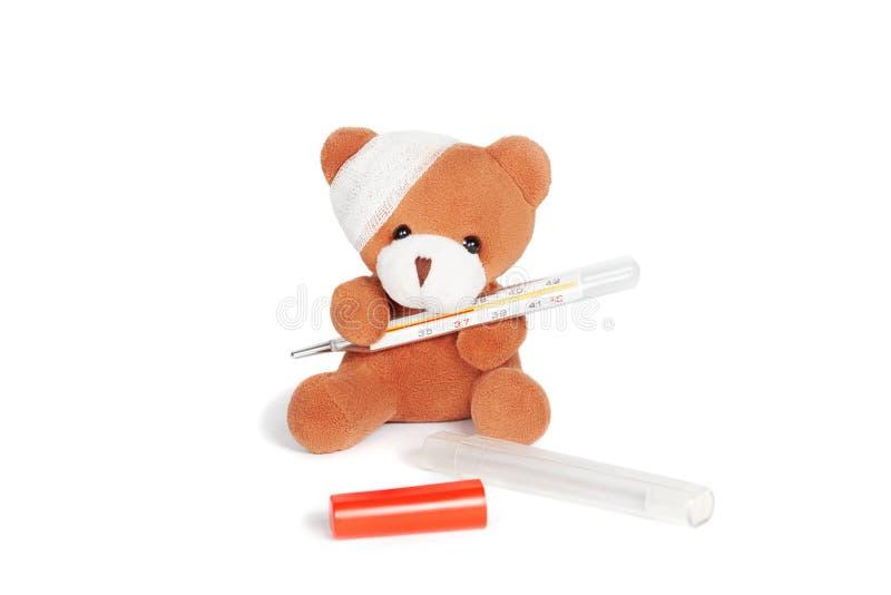 Nallebjörnen med förbinder och termometeren på vit royaltyfria bilder