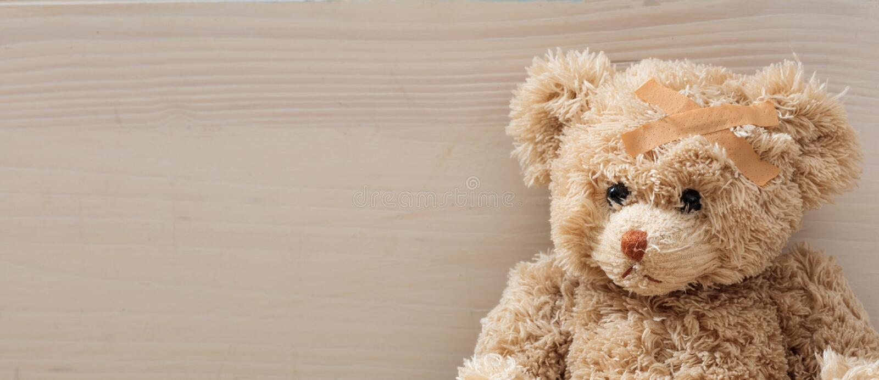 Nallebjörnen med förbinder på ett trägolv royaltyfri fotografi